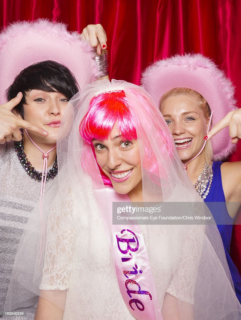 Women in photo booth, one wearing bridal veil : Stock Photo
