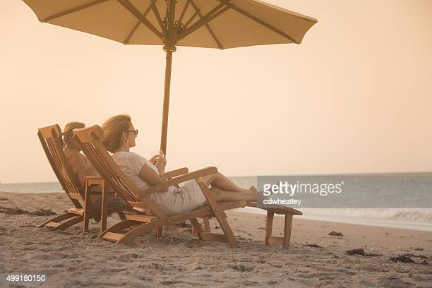 women in recliners enjoying a glass of wine and sunset