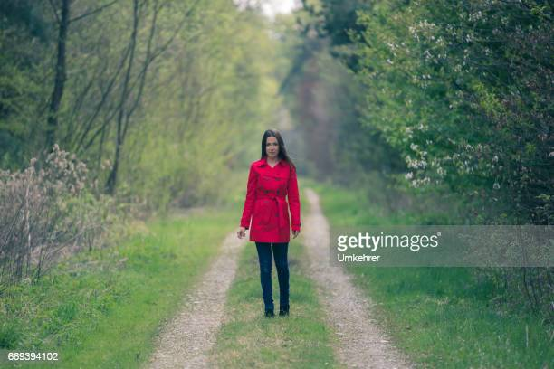 women in red coat stand on a path - multi colored coat stock photos and pictures