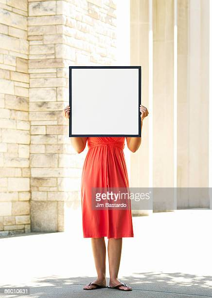 women in red with sign over face - possible stock pictures, royalty-free photos & images