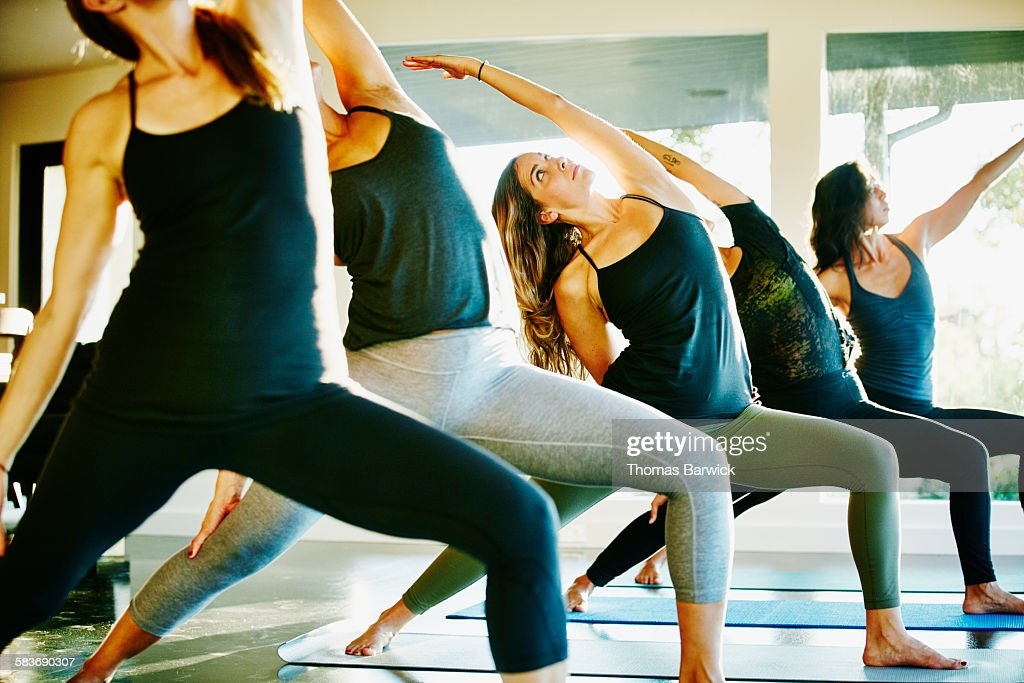 Women practicing yoga during class in studio in reverse warrior pose