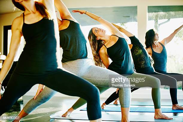 Women in reverse warrior pose during yoga class