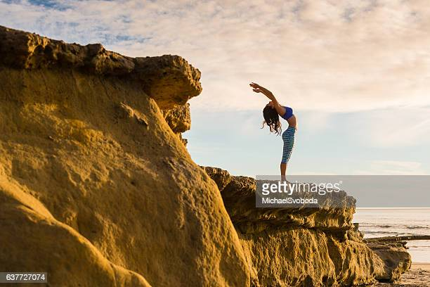 Women In Salutation Pose On A Bluff At The Ocean