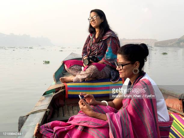 women in sari using mobile phones while sitting on boat - bangladesh stock pictures, royalty-free photos & images