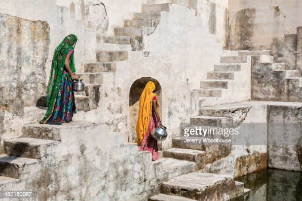 women in saris carrying water at step well, jaipur, rajasthan, india - stepwell stock photos and pictures