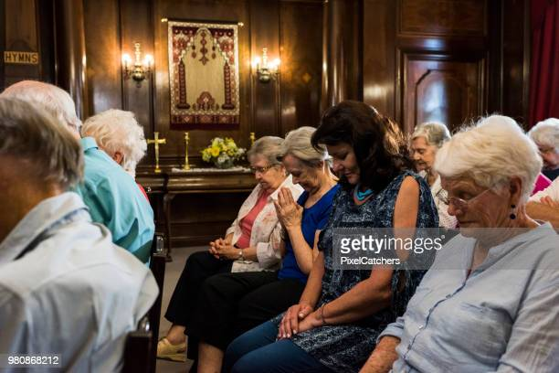 women in senior congregation praying together - church stock pictures, royalty-free photos & images