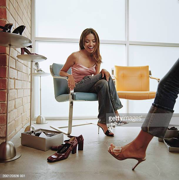 women in shoe store looking at friend trying on shoes - シューズボックス ストックフォトと画像