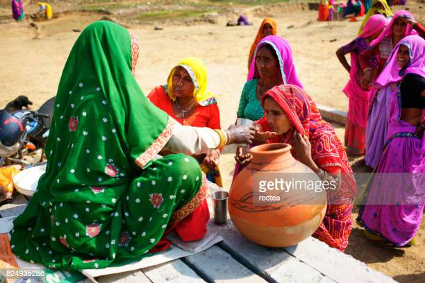 women in solidarity act provides water to another - scarce stock pictures, royalty-free photos & images