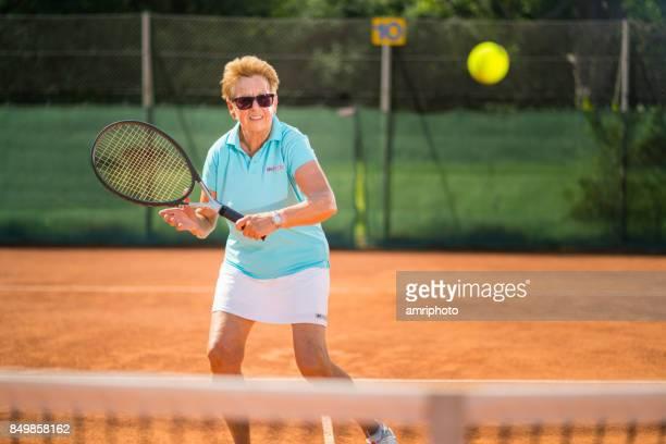 vrouwen in de sport - 70 jaar oude passen vrouw tennissen op zonnige dag - 70 79 jaar stockfoto's en -beelden