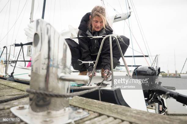 Women in Sport: female solo sailor in the harbor after  a day of sailing