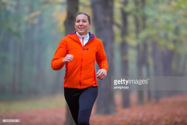 frauen im sport - schoß medium jogging frau im herbst - november stock-fotos und bilder