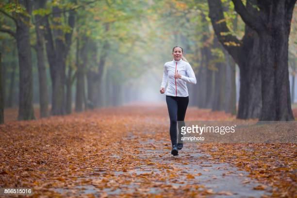 Women in Sport - running training in alley in autumn