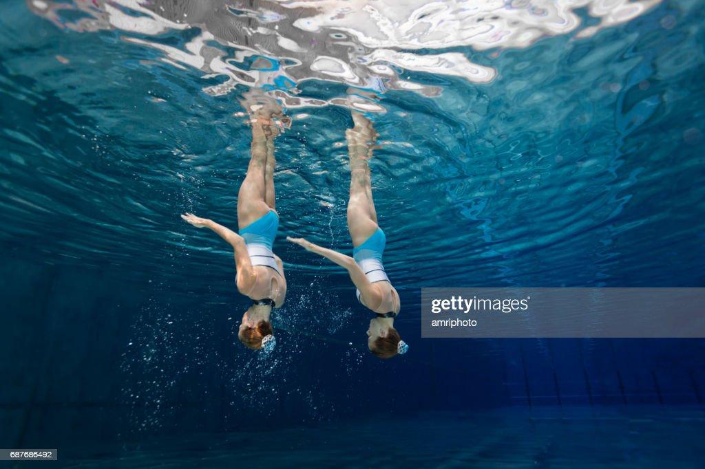Frauen im Sport, synchronisiert Teenager unter Wasser schwimmen : Stock-Foto