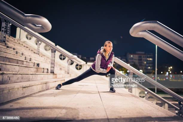 Women in Sport. Young, sporty woman exercising outdoors at night in a urban city area