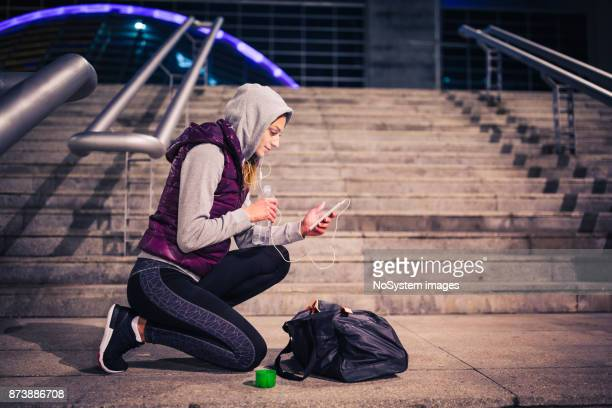 Women in Sport. Young woman taking break after sport training, listening  music, using smart phone