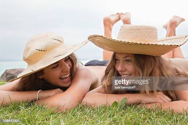 women in straw hats laughing together - girls sunbathing stock pictures, royalty-free photos & images