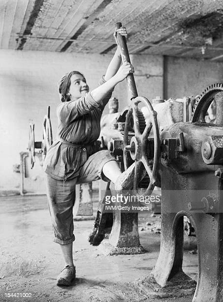 Women In The First World War, Industry, Transport and Agriculture: A girl dressed in trousers and overalls brings both arms and a foot to bear as she...
