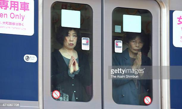 Women in the JR Takarazuka Line train observes a minute of silence as the train runs past the accident site on the 10th anniversary of the train...