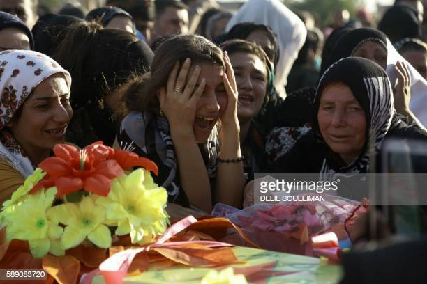 Women in the Kurdish-controlled city of Qamishli on August 13 mourn over a coffin during the funeral of several fighters from an Arab-Kurdish...