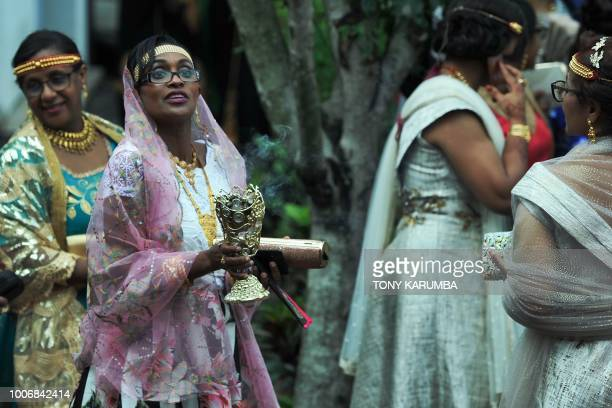 Women in their colourful garbs burn incense as they wait for the arrival of the groom at a traditional wedding ceremony in Moroni July 28 capital of...