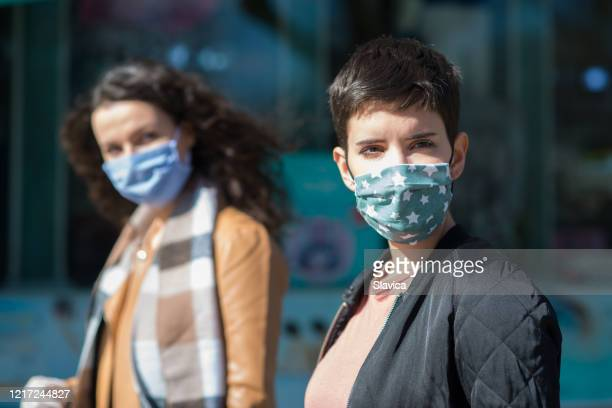 women in town wearing protective face masks and protective gloves - mascherina antipolvere foto e immagini stock