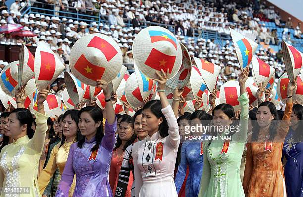 Women in traditional ao dai dress wave conical hats painted with national flags and the flag of the former Southern Viet Cong government as they...