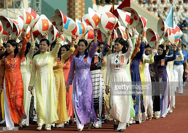 Women in traditional 'ao dai' dress wave conical hats painted with national flags and the flag of the former Southern Viet Cong government as they...
