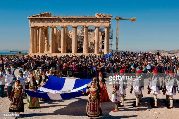 Women in traditional attire hold a Greek flag atop the Acropolis hill during a ceremony in front of the Parthenon temple marking the anniversary of...
