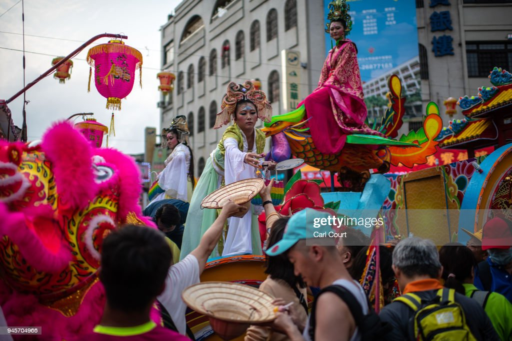 Women in traditional Chinese costumes handout candies to visitors as festivities begin to mark the nine day Mazu pilgrimage on April 13, 2018 in Dajia near Taichung, Taiwan. The annual Dajia Mazu Pilgrimage begins at Jenn Lann Temple in Taichung and sees around 200,000 pilgrims walk up to 12 hours each day for nine days carrying a statue of Chinese sea goddess Mazu in a sedan chair. The journey covers around 350 kilometres, much of it through mountainous and rugged terrain and visits more than 100 temples before returning to Taichung. The centuries-old pilgrimage is now recognised by UNESCO as living heritage and with an estimated 5 million participants spread over the nine days, it is considered to be one of the greatest religious festivals in the world.