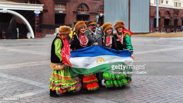 women in traditional clothing and male army soldier holding bashkortostan flag on footpath - hoofddeksel stockfoto's en -beelden