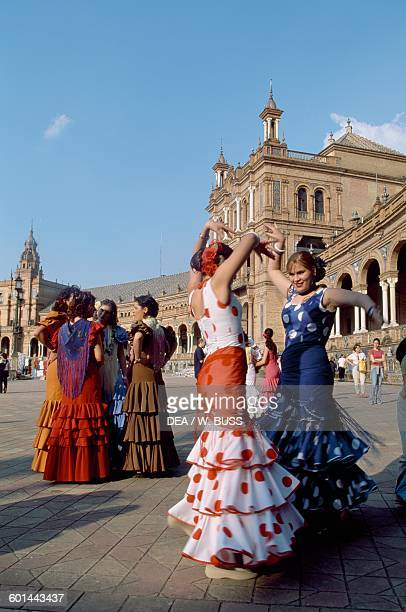 Women in traditional costumes dancing flamenco in the Plaza de Espana during the Feria de Abril Seville Andalusia Spain