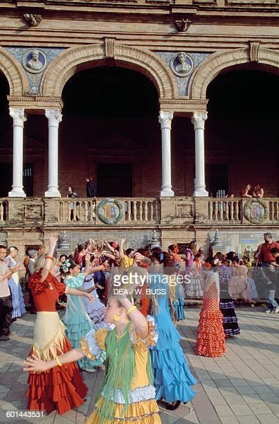 Women in traditional costumes dancing flamenco in the Plaza de Espana during the Feria de Abril Seville Andalusia Spain