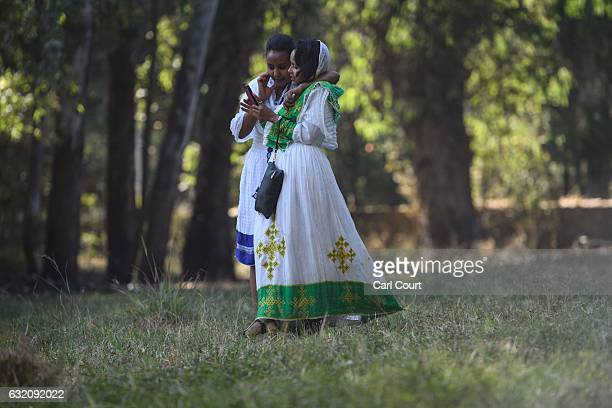 Women in traditional Ethiopian dress chat as they walk through a field during the annual Timkat Epiphany celebration on January 19 2017 in Gondar...