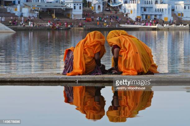 Women in traditional Indian clothing squatting on walkway near water