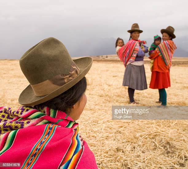 women in traditional peruvian dress carrying children - hugh sitton stockfoto's en -beelden