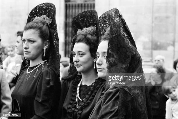 Women in traditional Spanish dress watch the celebrations for Holy Week underway in Seville as hooded penitents, known as 'Nazarenos' dressed in...