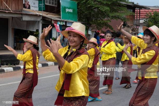 women in traditional thai clothes dancing in parade. - tim bewer stockfoto's en -beelden