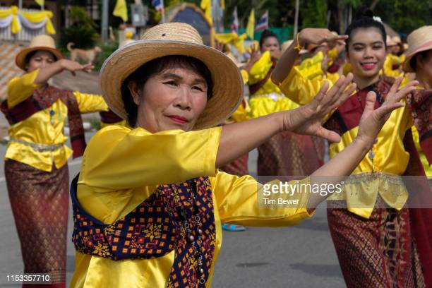 women in traditional thai clothes dancing in parade. - tim bewer stock pictures, royalty-free photos & images