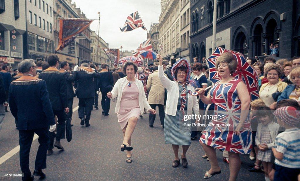 Women in Union Jack attire demonstrate alongside an Orange Order march in Belfast, Northern Ireland, circa July 1971.