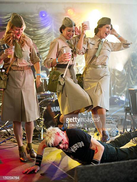 Women in wartime clothing pretend to stand on the lead singer of 1980s punk band 'Spizzenergi' as the band performs on the second day of 'Vintage at...