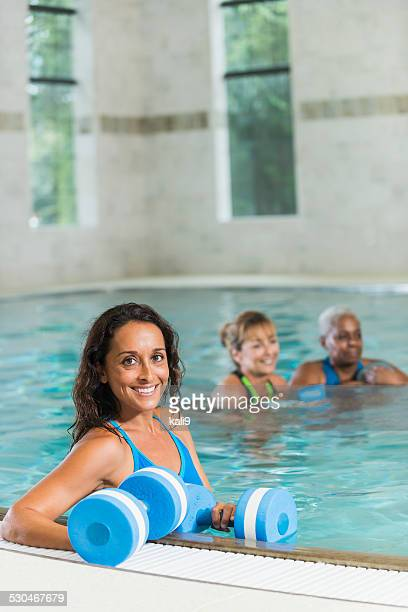 Women in water aerobics exercise class in swimming pool