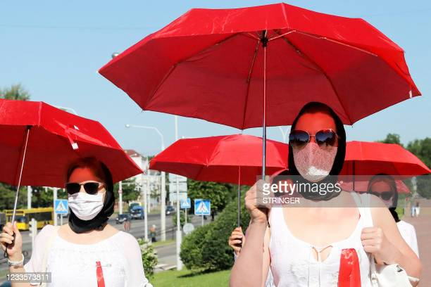 Women in white clothes walk down a street under red umbrellas, in reference to the colours of the former white-red-white flag of Belarus, to show...