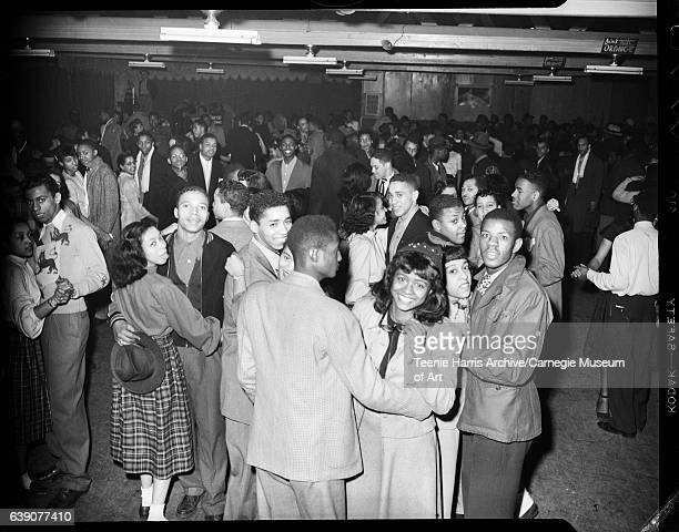 Women including several wearing plaid skirts and men dancing in interior of club with signs reading 'Drink Meadow Gold Grape' and 'Drink Meadow Gold...