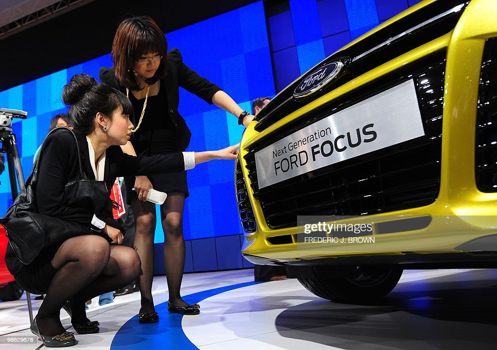 Women inspect the grill of a Ford Focus