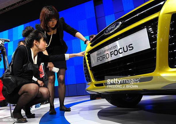 Women inspect the grill of a Ford Focus during a media preview at the Beiijng Auto Show on April 23 2010 Auto sales in booming China hit 1364 million...