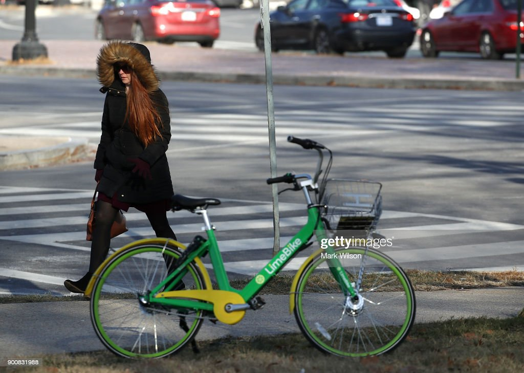 A women is bundled up as she walks past a bicycle on January 3, 2018 in Washington, DC. A winter storm is traveling up the east coast overnight with significant accumulationsÊof snow possible.