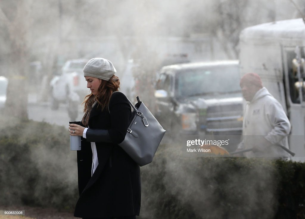A women is bundled up as she walks past a steam grate on January 3, 2018 in Washington, DC. A winter storm is traveling up the east coast overnight with significant accumulationsÊof snow possible.