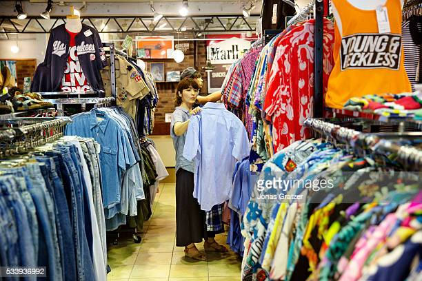 A women is looking at second hand clothing at a second hand shop in Tokyo Japan