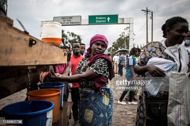 Women is seen washing her hands at an Ebola screening station as she enters the Democratic Republic of the Congo from Rwanda on July 16, 2019 in...