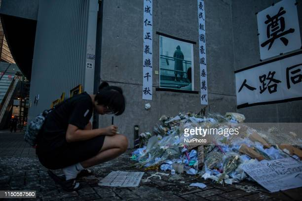 A Women is seen writing a peace of paper next to a memorial set up in Honor of a man who died after falling from a scaffolding in Pacific Place while...